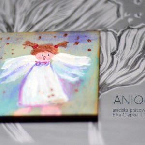 Drobny upominek w formie magnesu na lodówkę z aniołkiem ręcznie malowanym na sklejce brzozowej